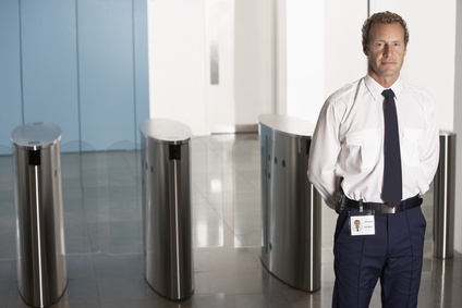 Security Guard Standing by Turnstiles